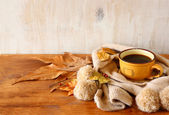 Top view of Cup of black coffee with autumn leaves, a warm scarf on wooden background. filreted image — Fotografia Stock