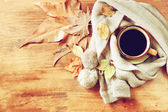 Top view of Cup of black coffee with autumn leaves, a warm scarf on wooden background. filreted image — Stock Photo