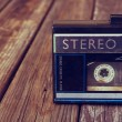 Old portable cassette player on a wooden background. image is instagram style filtered — Stock Photo #58567335