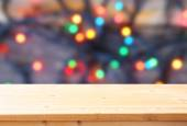 Rustic wood table in front of glitter colorfull bright bokeh lights — Stock Photo