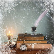 Low key image of white Feather, inkwell, old books and candle and glitter lights background on old wooden table  with snowflake overlay — Stock Photo #59623591