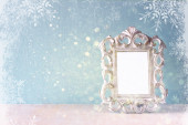 Low key image of vintage antique classical frame on wooden table and glitter lights background with snowflake overlay . filtered image — Stock Photo