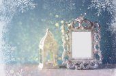 Low key image of vintage antique classical frame and Burning candle on wooden table and glitter lights background with snowflake overlay . filtered image — Stock Photo