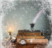 Low key image of white Feather, inkwell, old books and candle and glitter lights background on old wooden table  with snowflake overlay — Stock fotografie