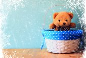 Toy teddy bear in basket on wooden table with snowflake overlay — Stock Photo