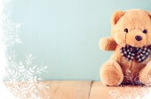 Toy teddy bear in basket on wooden table with snowflake overlay — Stockfoto