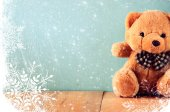 Toy teddy bear in basket on wooden table with snowflake overlay — 图库照片