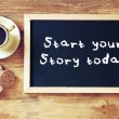 Top view of blackboard with the phrase start your story today next to cup of black coffee and cookies — Stock Photo #59749997