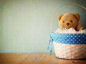 Toy teddy bear in basket on wooden table. retro filtered image — Stockfoto