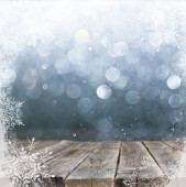 Rustic wooden table in front of silver and white bokeh defocused lights with snowflake . abstract background — Stock Photo