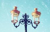 Picture of an antique street lamp against blue sky. vintage filtered image and bokeh lights. — Stock Photo