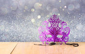 Mysterious Venetian masquerade mask on wooden table and glitter background — Stock Photo