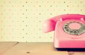 Retro pastel pink telephone on wooden table and abstract retro geometric pastel pattern Background. retro filtered image — Stockfoto
