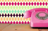 Retro pastel pink telephone on wooden table and abstract retro geometric pastel pattern Background. retro filtered image — Stock Photo
