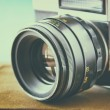 Close up photo of old camera lens over wooden table. image is retro filtered. selective focus — Stock Photo #63202233