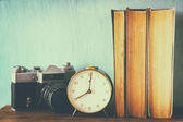 Stack of books, old clock and vintage camera over wooden table. image is processed with retro faded style — Stock Photo