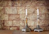 Two candlesticks with burning candles over wooden table and old jerusalem stone wall background — Photo