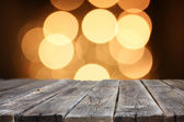Rustic wood table in front of glitter gold bright bokeh lights — Stock Photo