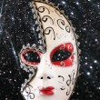 Dramatic and mysterious half moon carnival mask and black glitter background — Stock Photo #66078805