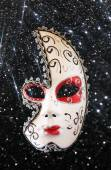 Dramatic and mysterious half moon carnival mask and black glitter background — Stock Photo