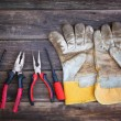 Top view of worn work gloves and assorted work tools over wooden background — Stock Photo #66859641