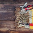Top view of worn work gloves and assorted work tools over wooden background — Stock Photo #66859879