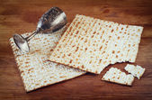 Passover background. wine cup and matzoh (jewish passover bread) over wooden background. — Stock Photo