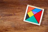 Вид сверху кусок отсутствует в квадратных Танграм головоломки, над деревянным столом. — Стоковое фото