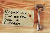 The phrase - unlock the golden door of freedom written on note attached to key — Stock Photo