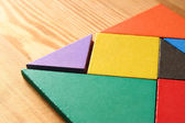 A missing piece in a square tangram puzzle, over wooden table. — Stock Photo