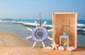 Antiguo náutica madera rueda, ancla y cáscaras en mesa de madera sobre el fondo del mar — Foto de Stock