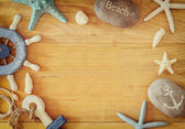 Collection of nautical and beach objects creating a frame over wooden background, — Stock Photo