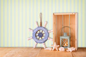 Old nautical wood wheel, anchor and shells on wooden table over retro background — Stock Photo