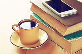 Cup of coffee, stack of old books and smartphone over wooden table, retro filtered image — Stock Photo