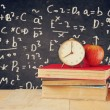 Image of school books on wooden desk, apple and vintage clock over black background with formulas. education concept — Stock Photo #71156659