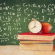 Image of school books on wooden desk, apple and vintage clock over green background with formulas. education concept — Stock Photo #71156711