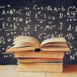 Image of school books on wooden desk over black background with formulas. education concept — Stock Photo #71157177