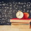 Image of school books on wooden desk, apple and vintage clock over black background with formulas. education concept — Stock Photo #71157287