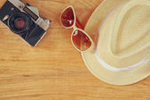 Top view of stylish hat woman sunglasses old camera over wooden table. vaction and travel concept — Stock Photo
