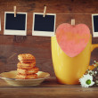 Photo frames hanging on a rope with coffee cup and cookies over wooden background — Stock Photo #73796003