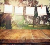 Alte Polaroid-Foto-Rahmen, hängend an einem Seil mit Jahrgang Holzbrett Tisch vor abstrakten Waldlandschaft — Stockfoto