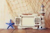 Old vintage wooden white fram lighthouse on wooden table. vintage filtered image. nautical lifestyle concept — Stock Photo