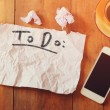 Top view image of blank paper with the text to do in hand write, next to cellphone and coffee cup over wooden table — Stock Photo #74084389
