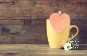 Yellow mag with a wooden vintage pink heart on wooden table — Stock Photo