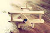 Wooden airplane toy over textured wooden background. retro style image — Stock Photo