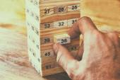 Male hand placing wooden block on a tower. planing and strategy concept — Stock Photo