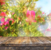 Wood board table in front of summer landscape with double exposure of flower bloom — Stock Photo