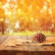 Autumn background of fallen leaves over wooden table and forest backgrond with lens flare and sunset. — Photo #83821464