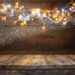 Wood board table in front of Christmas warm gold garland lights on wooden rustic background. filtered image. selective focus. glitter overlay. — Stock Photo #84707042