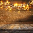 Wood board table in front of Christmas warm gold garland lights on wooden rustic background. filtered image. selective focus. glitter overlay. — Stock Photo #84707656